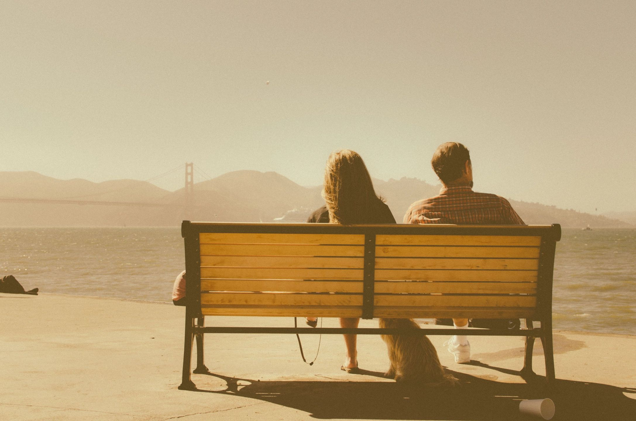 A young couple sits on a park bench that overlooks a city skyline.